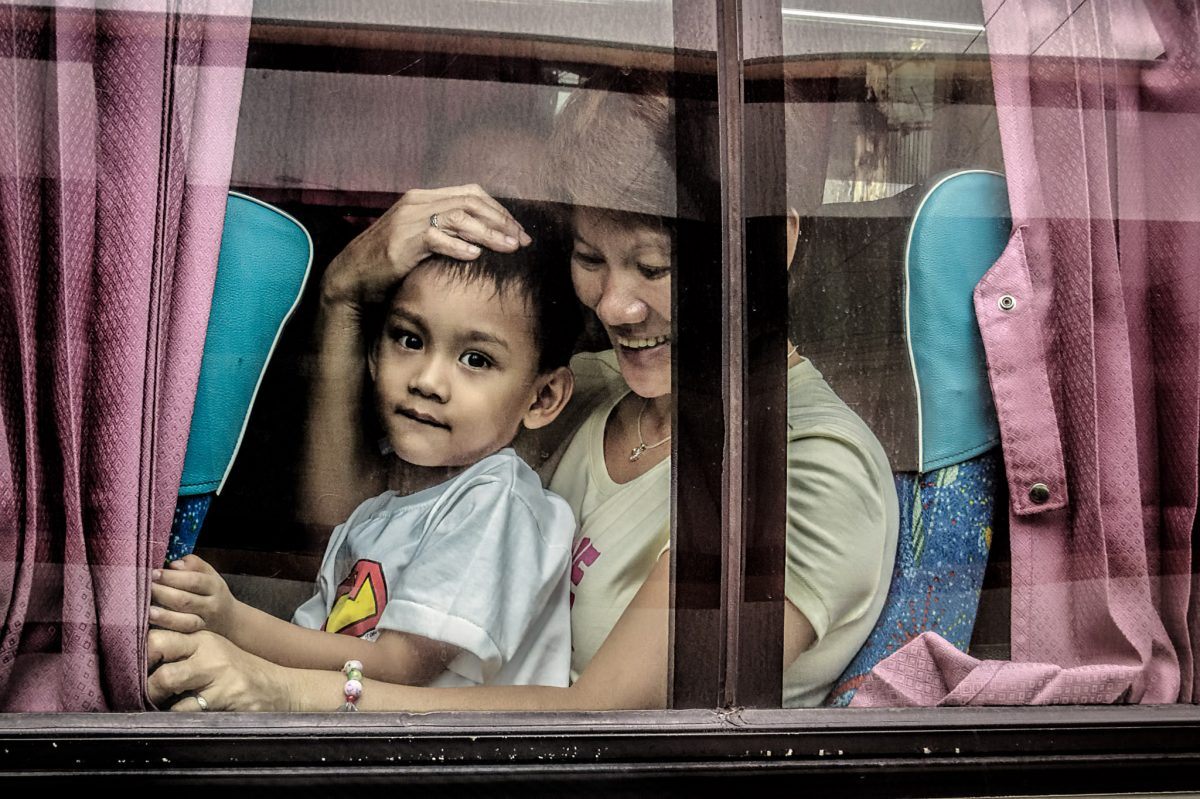 Mother and son share a seat on the Manila to Bulacan bus.  It's common for a child to sit on their parent's lap to make room for more passengers.